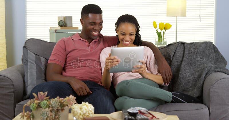 Счастливые черные пары смеясь над и используя таблеткой стоковые изображения