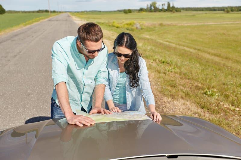 Счастливые человек и женщина с дорожной картой на клобуке автомобиля стоковые изображения