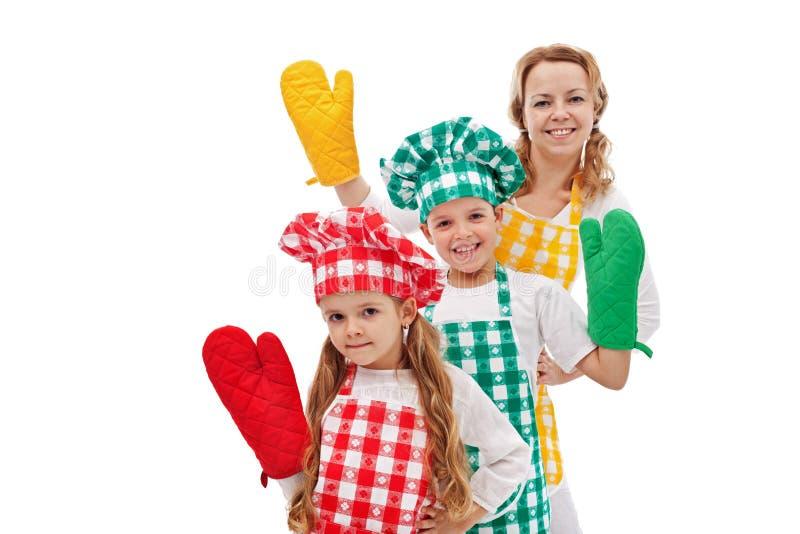 Счастливые шеф-повара развевая к вам - дети с большими перчатками кухни стоковое изображение rf
