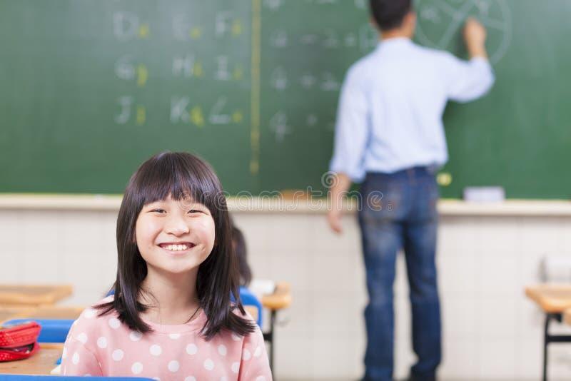 Счастливые школьники в классе с учителем стоковое фото rf