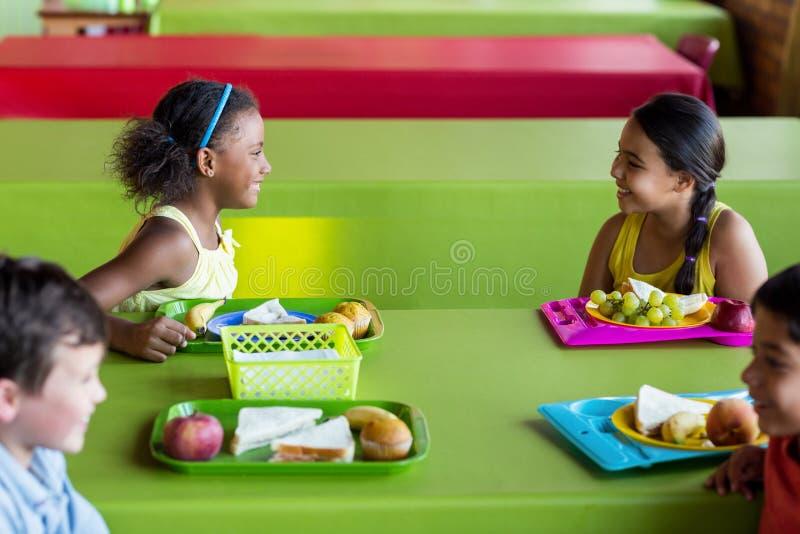 Счастливые школьники имея завтрак стоковое изображение