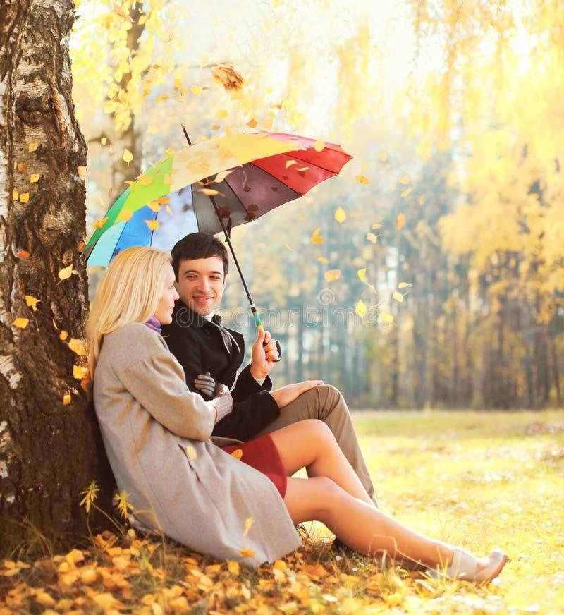 Счастливые любящие молодые пары сидя под деревом с красочным зонтиком в листьях солнечного дня падая стоковое фото