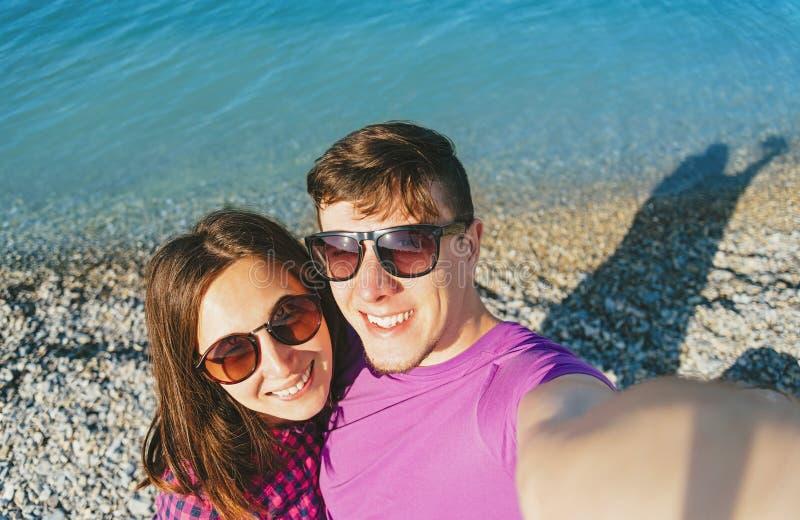 Счастливые любящие пары делая автопортрет на пляже стоковая фотография rf
