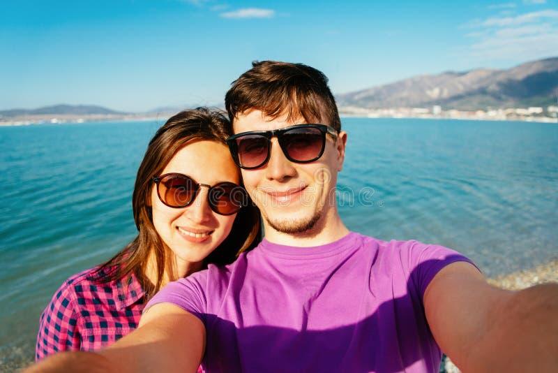 Счастливые любящие пары принимая автопортрет на пляже стоковое фото
