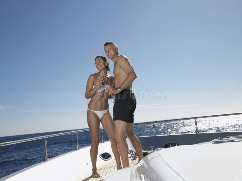 Счастливые любящие пары стоя на яхте стоковые фото