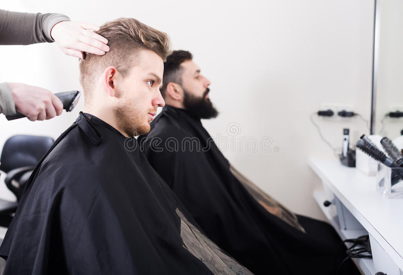 Счастливые люди имея их волосы быть отрезанным парикмахерами стоковое изображение rf