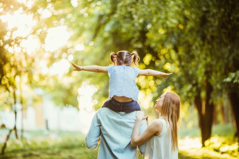 Счастливые люди семьи из трех человек идя трава в парке на заходе солнца счастливое летание дочери на задней части отца стоковое фото rf