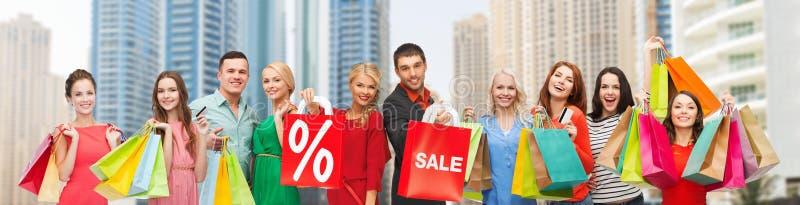 Счастливые люди с продажей подписывают показывать большие пальцы руки вверх стоковое фото rf