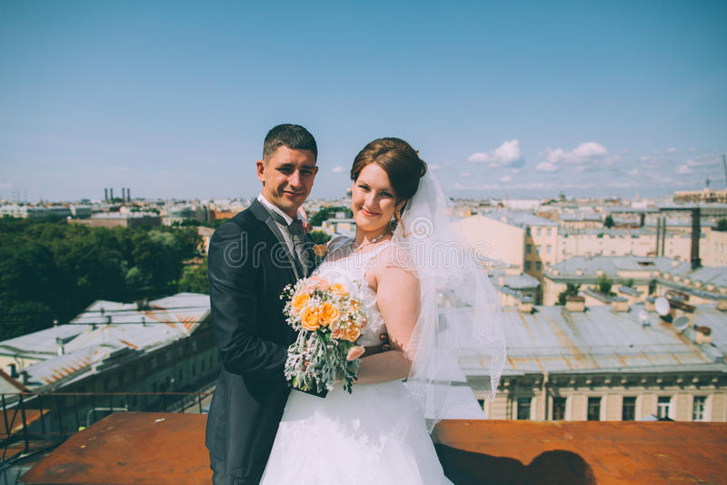 Счастливые groom и невеста стоят на крыше стоковая фотография
