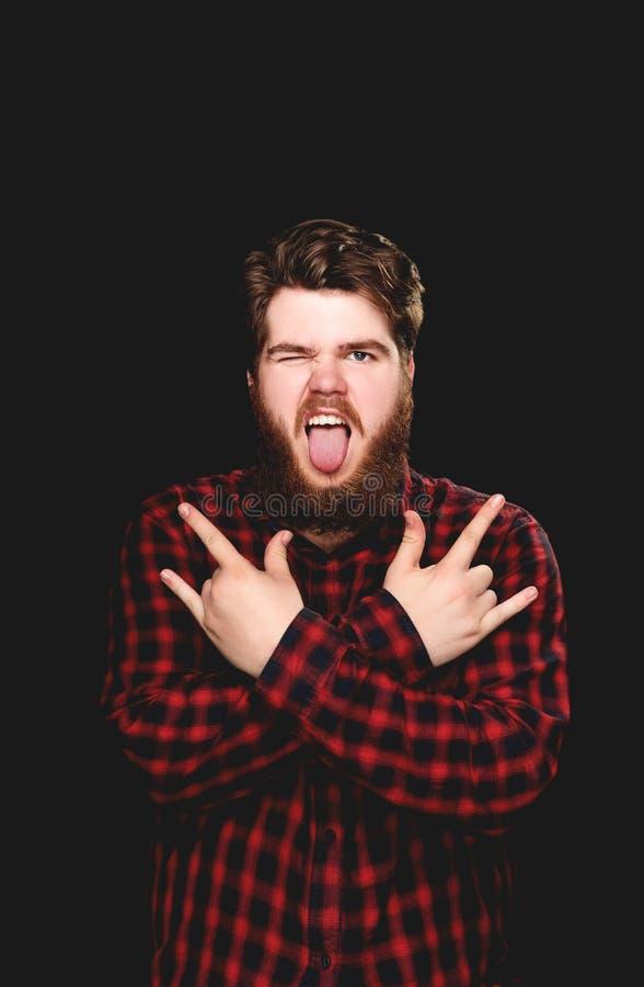 Счастливые winks парня показывая его язык с жестом утеса в наличии стоковые изображения