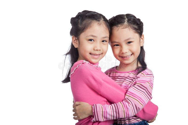 Счастливый азиатский двойной один другого объятия сестер стоковое фото