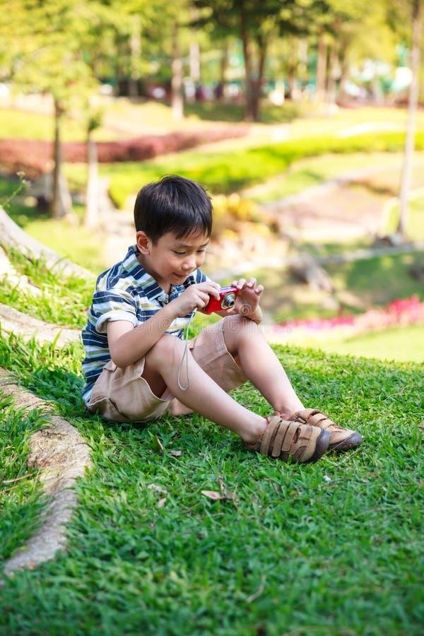 Счастливый азиатский мальчик при камера ослабляя outdoors во времени дня, t стоковые изображения