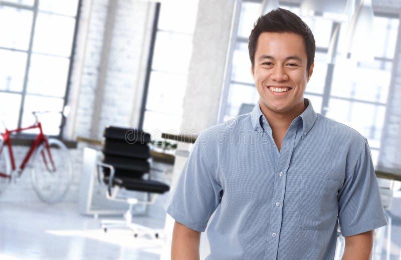 Счастливый азиатский работник офиса на ультрамодном рабочем месте стоковые изображения