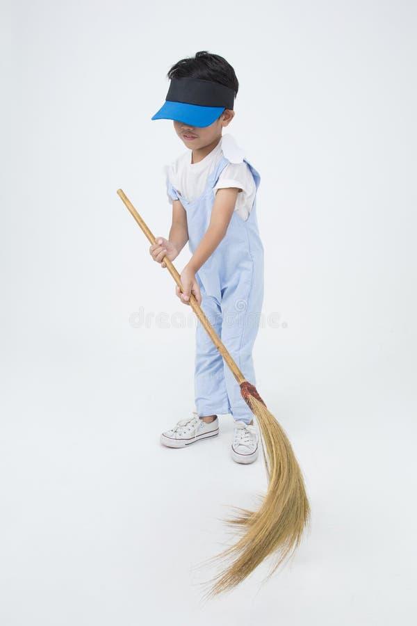 Счастливый азиатский ребенок с чисткой веника в доме стоковые фото