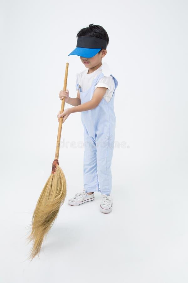 Счастливый азиатский ребенок с чисткой веника в доме стоковая фотография rf