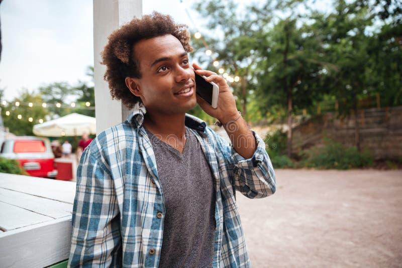 Счастливый африканский молодой человек говоря на сотовом телефоне outdoors стоковое изображение