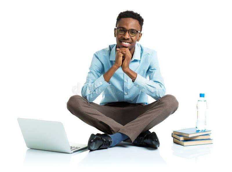 Счастливый Афро-американский студент колледжа сидя на белизне с подолом стоковые фотографии rf