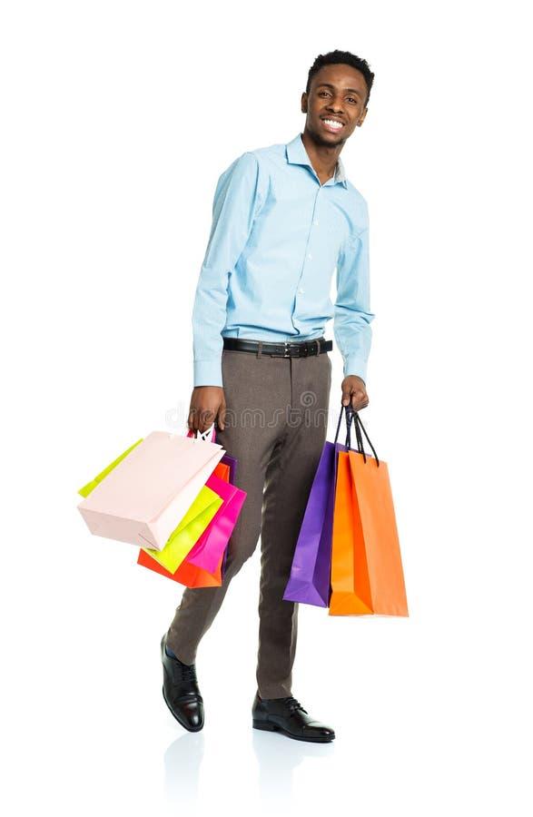 Счастливый Афро-американский человек держа хозяйственные сумки на белом backgr стоковая фотография