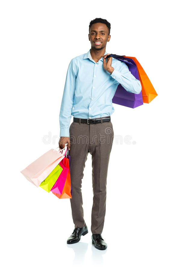 Счастливый Афро-американский человек держа хозяйственные сумки на белизне Holid стоковые изображения rf