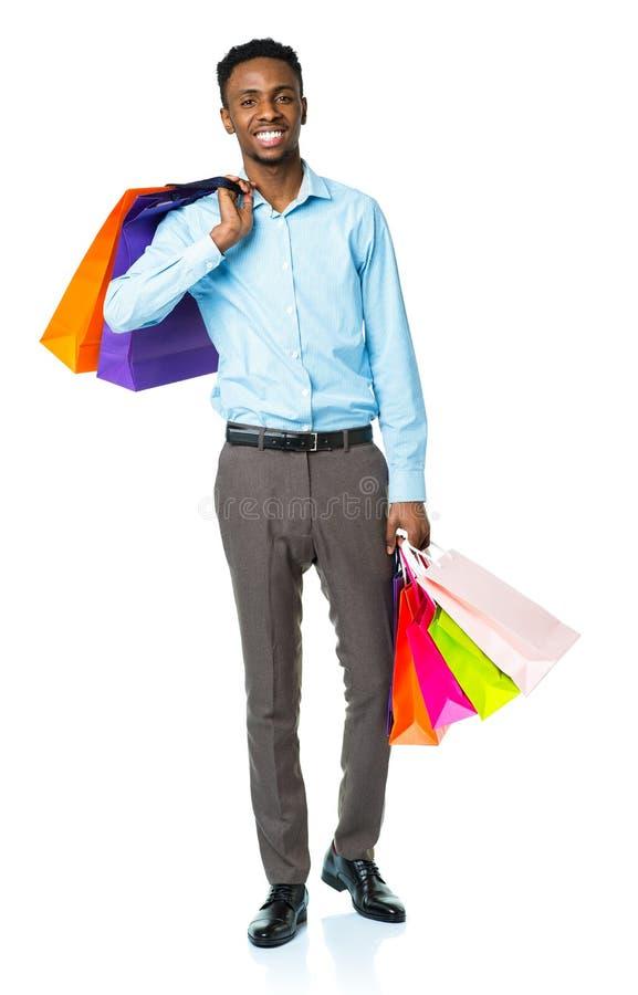 Счастливый Афро-американский человек держа хозяйственные сумки на белом backgr стоковые изображения