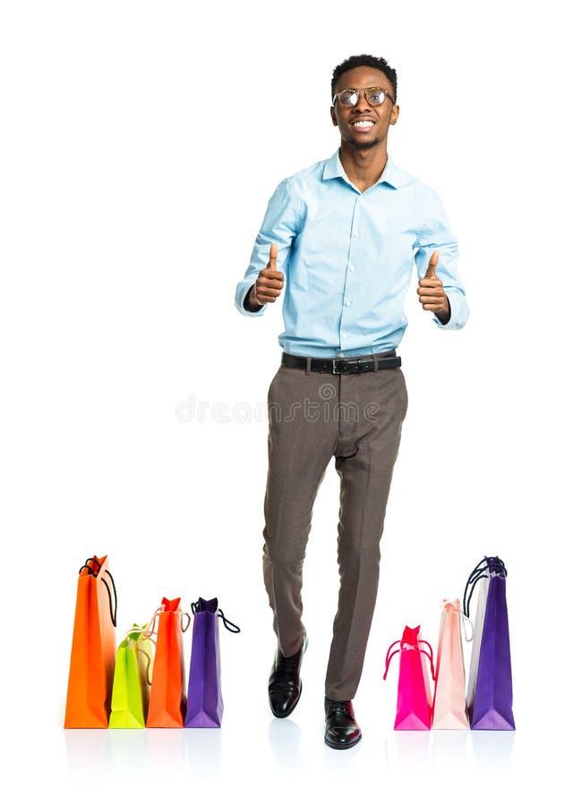 Счастливый Афро-американский человек с большими пальцами руки поднимает и хозяйственные сумки на w стоковая фотография rf
