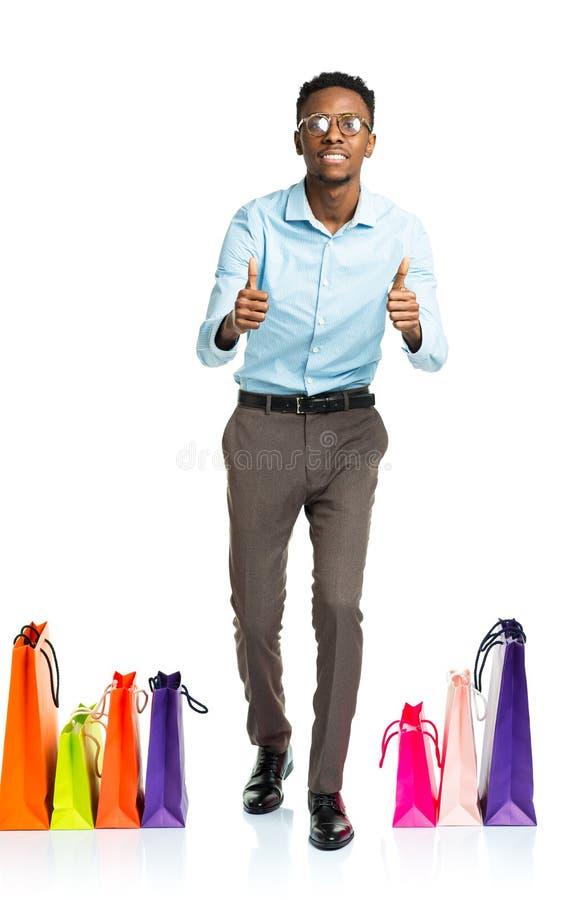 Счастливый Афро-американский человек с пальцами поднимает и хозяйственные сумки дальше стоковое изображение