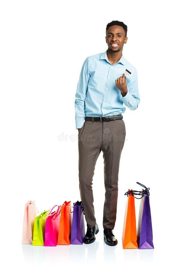 Счастливый Афро-американский человек с хозяйственными сумками и credi держать стоковое фото