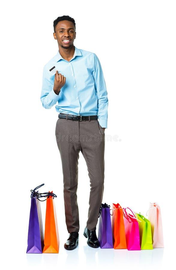 Счастливый Афро-американский человек с хозяйственными сумками и credi держать стоковое изображение