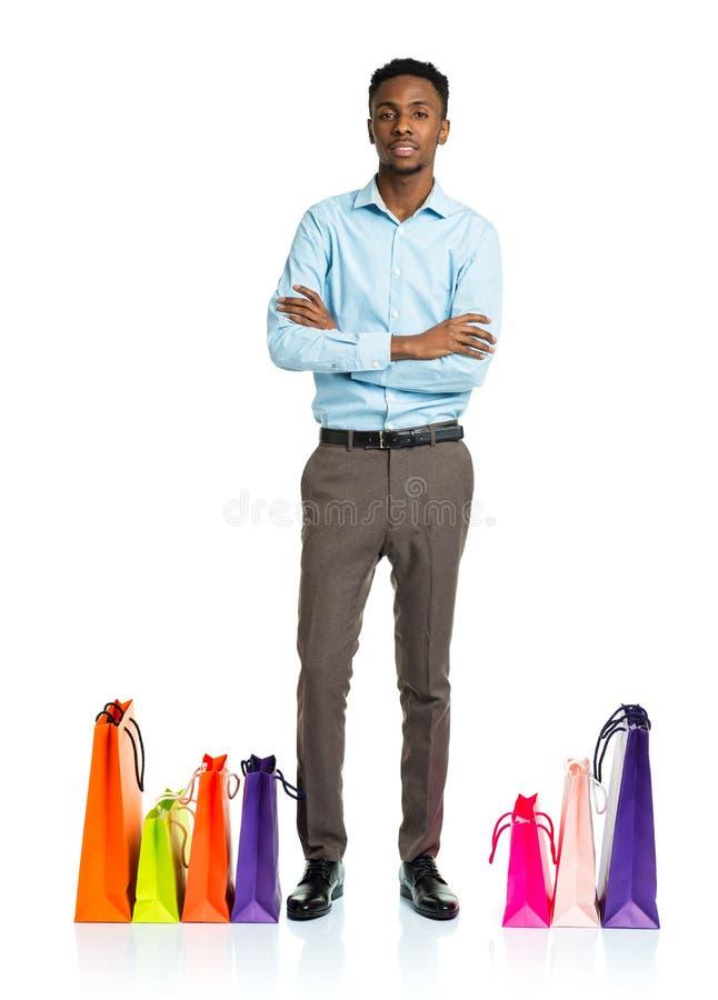 Счастливый Афро-американский человек с хозяйственными сумками на белом backgroun стоковые изображения