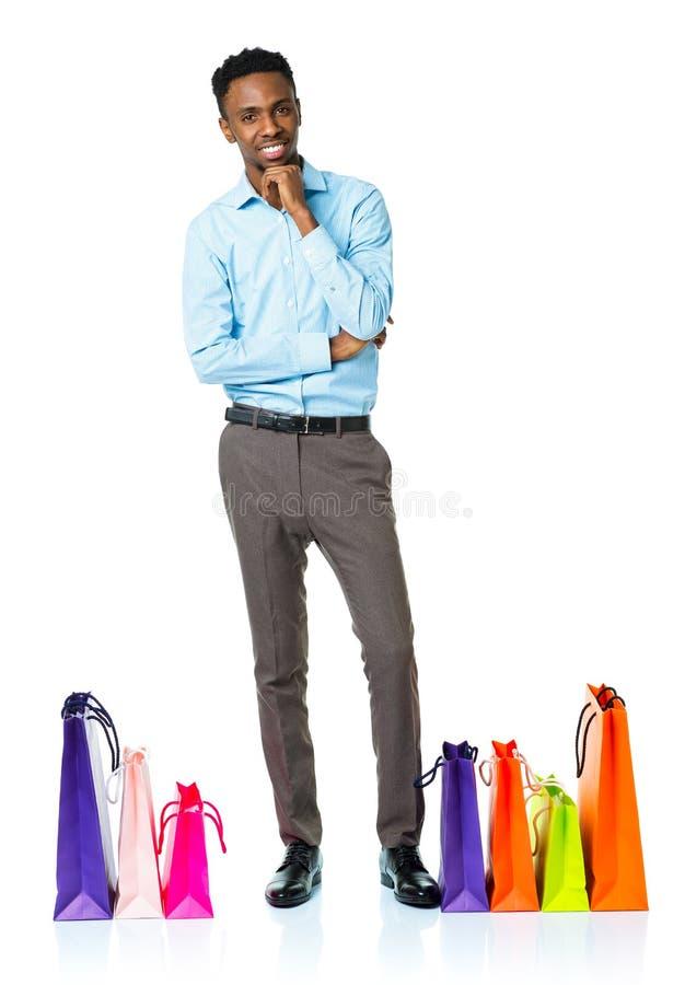 Счастливый Афро-американский человек с хозяйственными сумками на белом backgroun стоковые фотографии rf