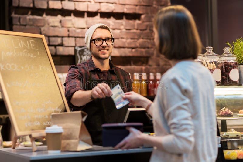 Счастливый бармен и женщина оплачивая деньги на кафе стоковое изображение rf