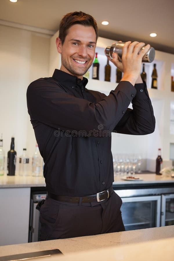 Счастливый бармен тряся коктеиль стоковое фото