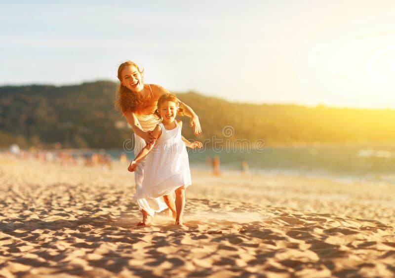 Счастливый бег матери и дочери семьи, смех и игра на пляже стоковое изображение