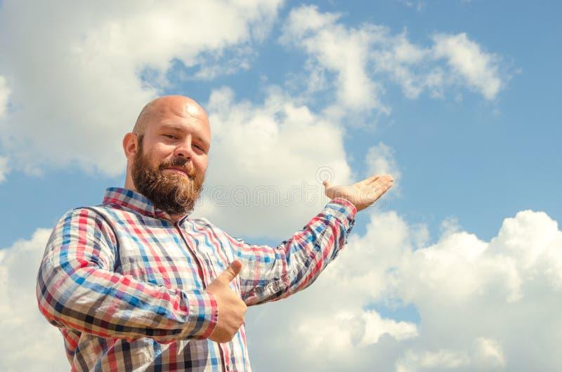 Счастливый безволосый человек с бородой указывая к пасмурному красивому небу стоковые фото