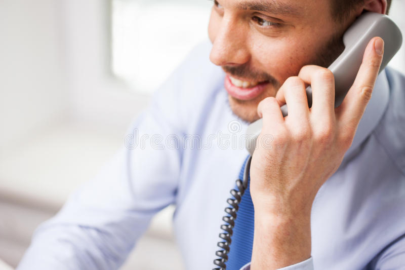 Счастливый бизнесмен вызывая на телефоне на офисе стоковое изображение