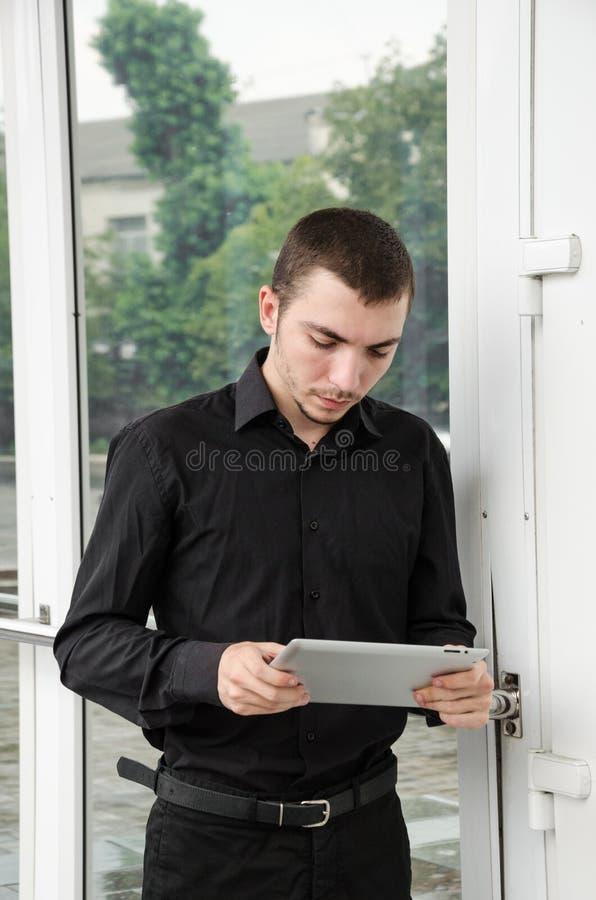 Счастливый бизнесмен в черном костюме с цифровой таблеткой на офисе стоковое изображение rf