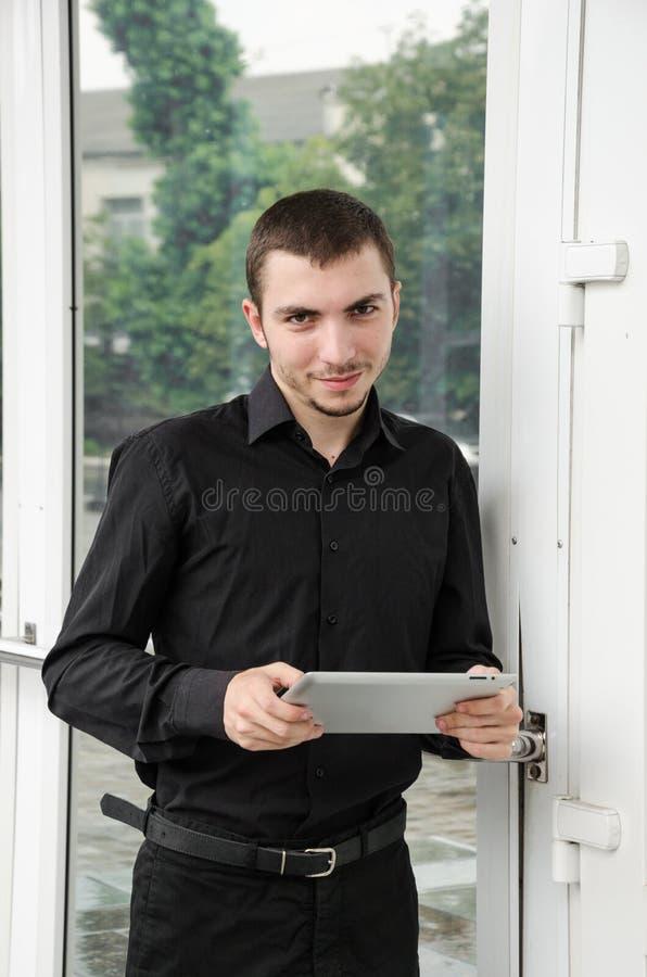 Счастливый бизнесмен в черном костюме с цифровой таблеткой на офисе стоковые изображения