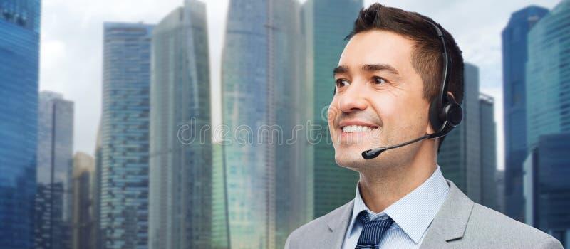 Счастливый бизнесмен в шлемофоне над предпосылкой города стоковое изображение