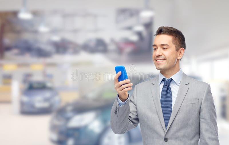 Счастливый бизнесмен отправляя СМС на smartphone стоковая фотография