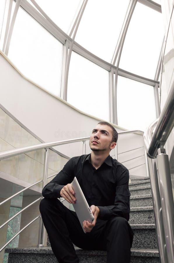 Счастливый бизнесмен сидя на лестницах с цифровой таблеткой в офисе и смотрит вверх стоковое фото