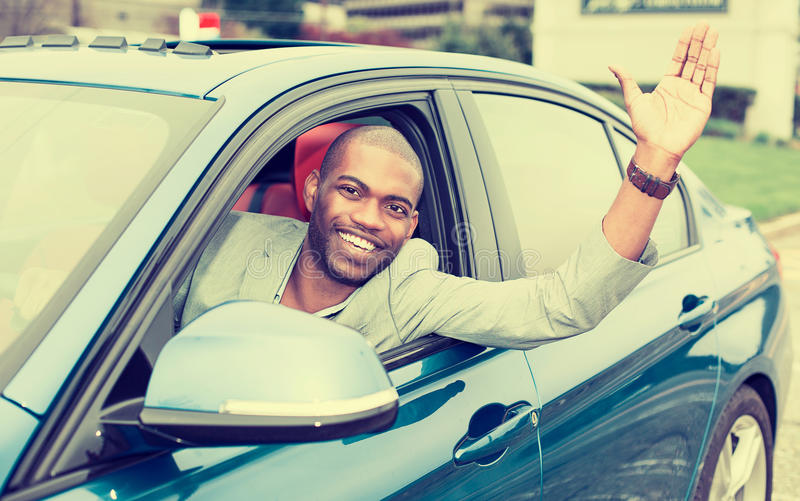 Счастливый водитель молодого человека вставил его руку из окна автомобиля стоковые фотографии rf