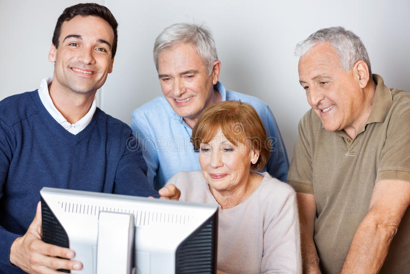 Счастливый гувернер помогая старшим людям в использовании компьютера на классе стоковые изображения