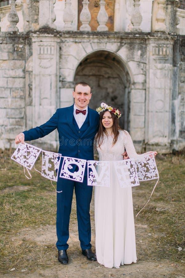 Счастливый жених и невеста держа художнические любовные письма papercut стоковое фото