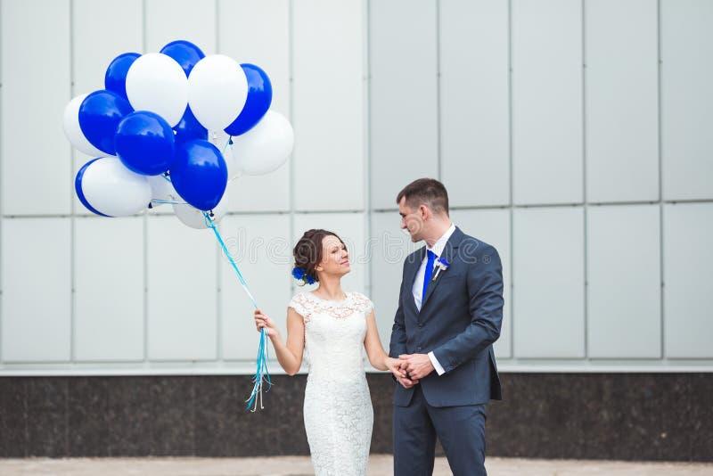 Счастливый жених и невеста празднуя день свадьбы с воздушными шарами стоковая фотография