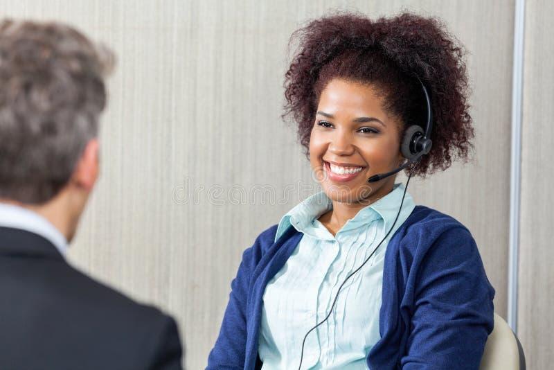 Счастливый женский агент обслуживания клиента смотря стоковое изображение rf