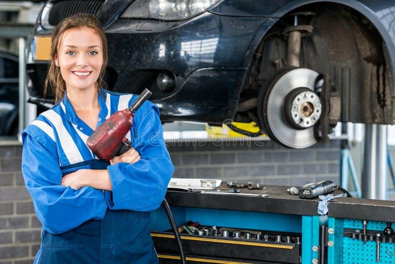 Счастливый женский механик держа пневматический ключ автомобилем стоковые фото