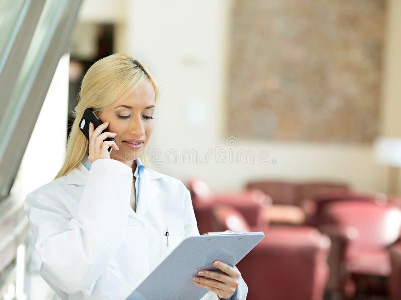 Счастливый женский доктор говоря к пациенту на телефоне стоковые фото