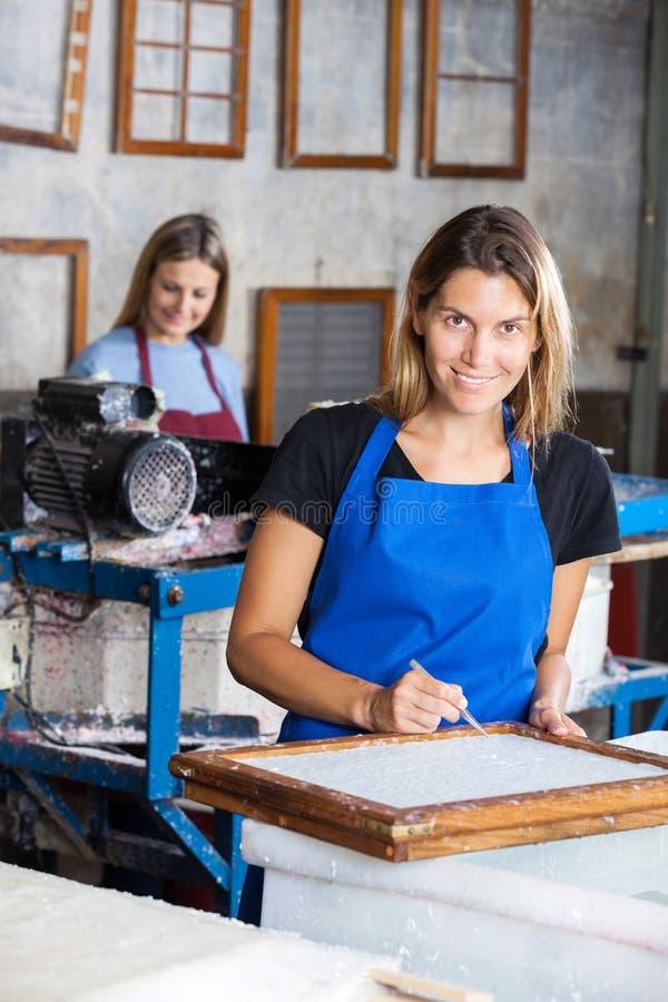 Счастливый женский работник используя щипчики для того чтобы очистить бумагу на прессформе стоковое фото