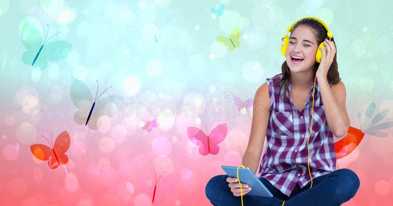 Счастливый женский слушать к музыке через наушники используя ПК таблетки над предпосылкой бабочки стоковое изображение