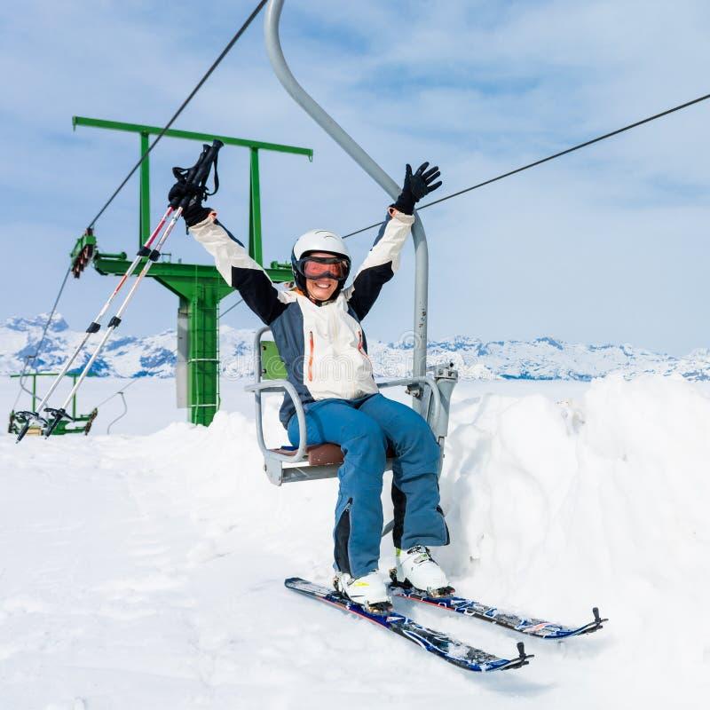 Счастливый женский лыжник ехать подъем стоковое изображение rf